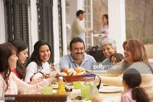 Hispanic family eating dinner outdoors