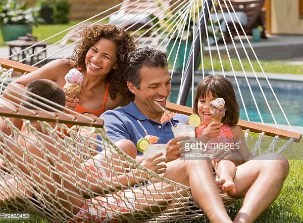 Hispanic family eating ice cream in hammock