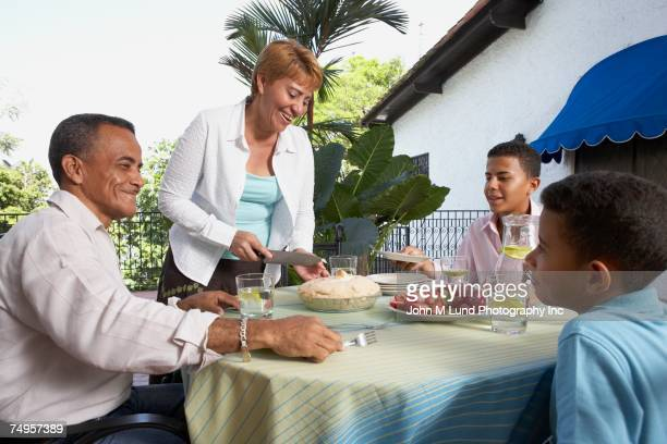 Hispanic family eating pie outdoors