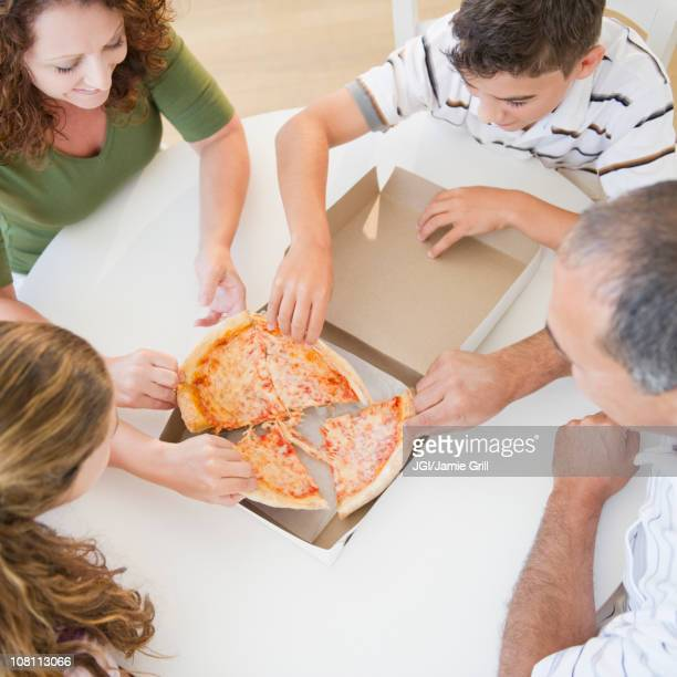 Hispanic family eating pizza together