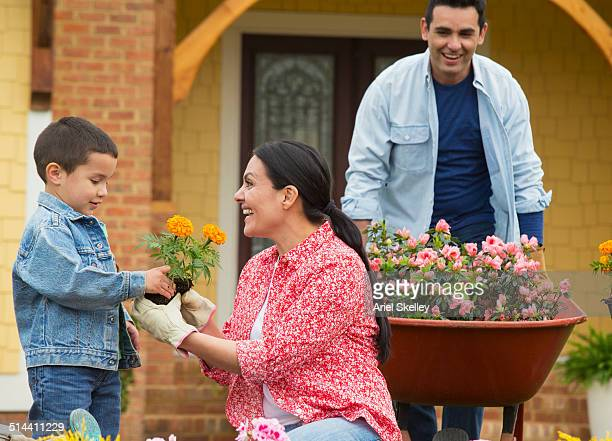 Hispanic family gardening together in front yard