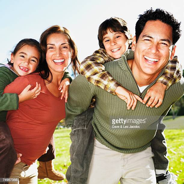 Hispanic family giving piggy back rides in park