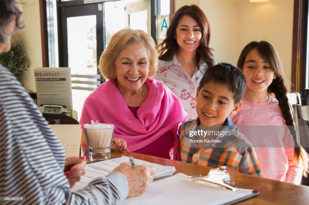 Hispanic family greeting host at restaurant