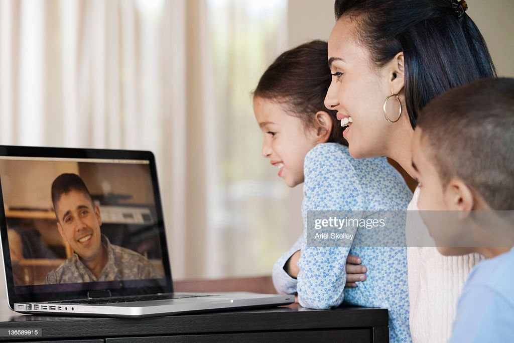 Hispanic family having video chat with military father : Stock Photo