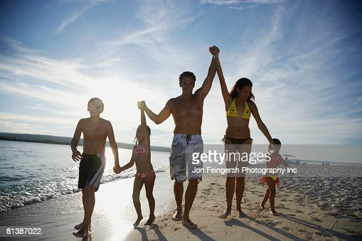 Hispanic family holding hands at beach : Stock Photo