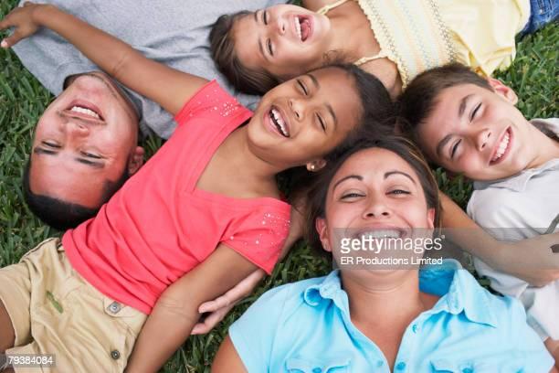 Hispanic family laying in grass
