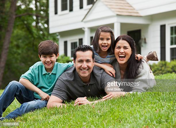 Hispanic family laying on grass in front yard