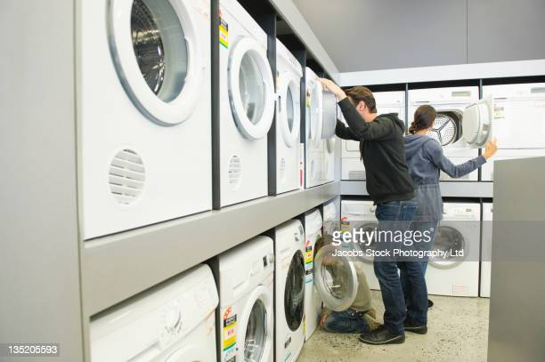 Hispanic family looking at washing machines in department store