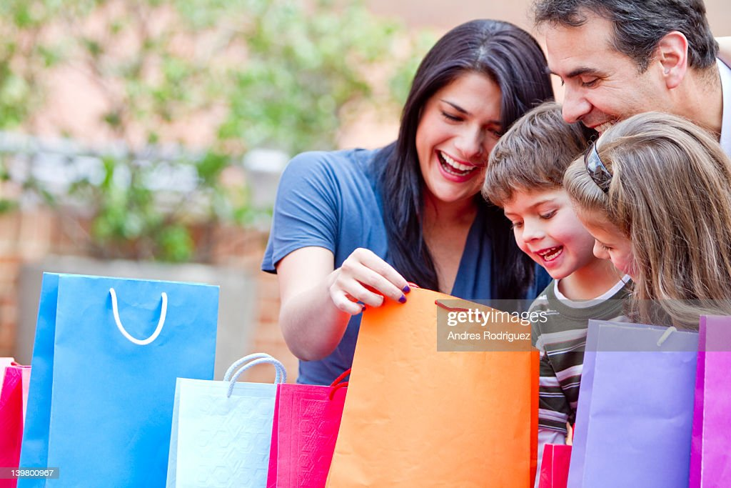 Hispanic family looking into shopping bags : Stock Photo