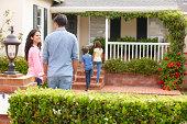 Hispanic family standing in front garden outside home