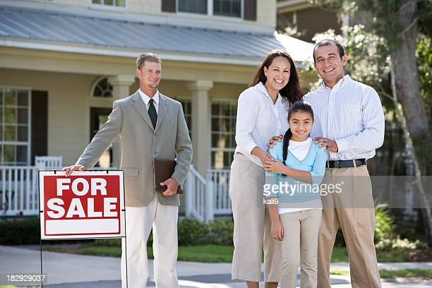 Hispanic family outside house for sale with real estate agent