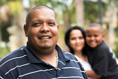 Hispanic man posing smiling with his wife and son in the background