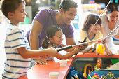 Hispanic family playing arcade game in amusement park