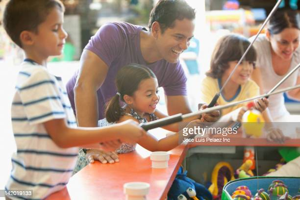 Hispanic family playing arcade game in amusement park