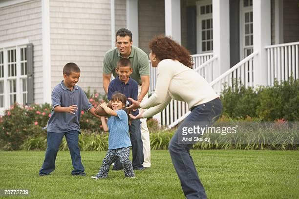 Hispanic family playing football in backyard