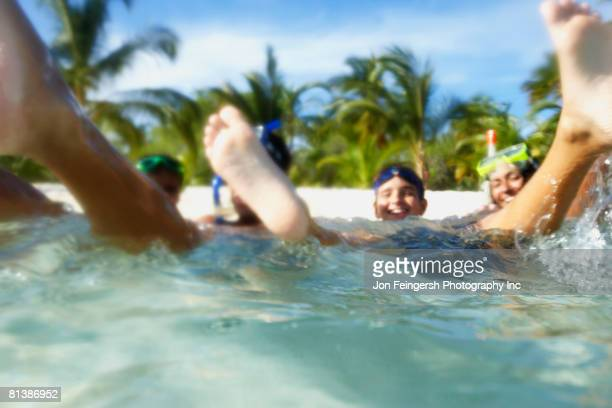 Hispanic family playing in water