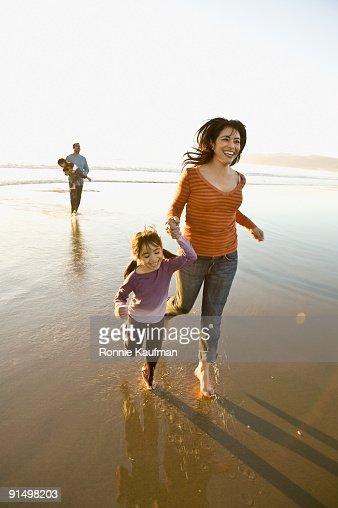 Hispanic family playing on beach : Stock Photo