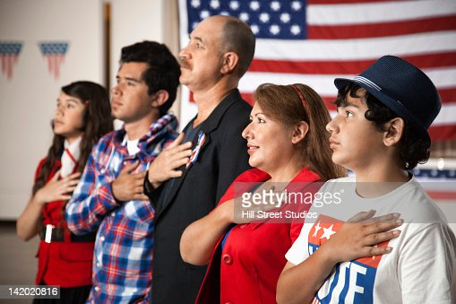 Hispanic family pledging allegiance to the American flag