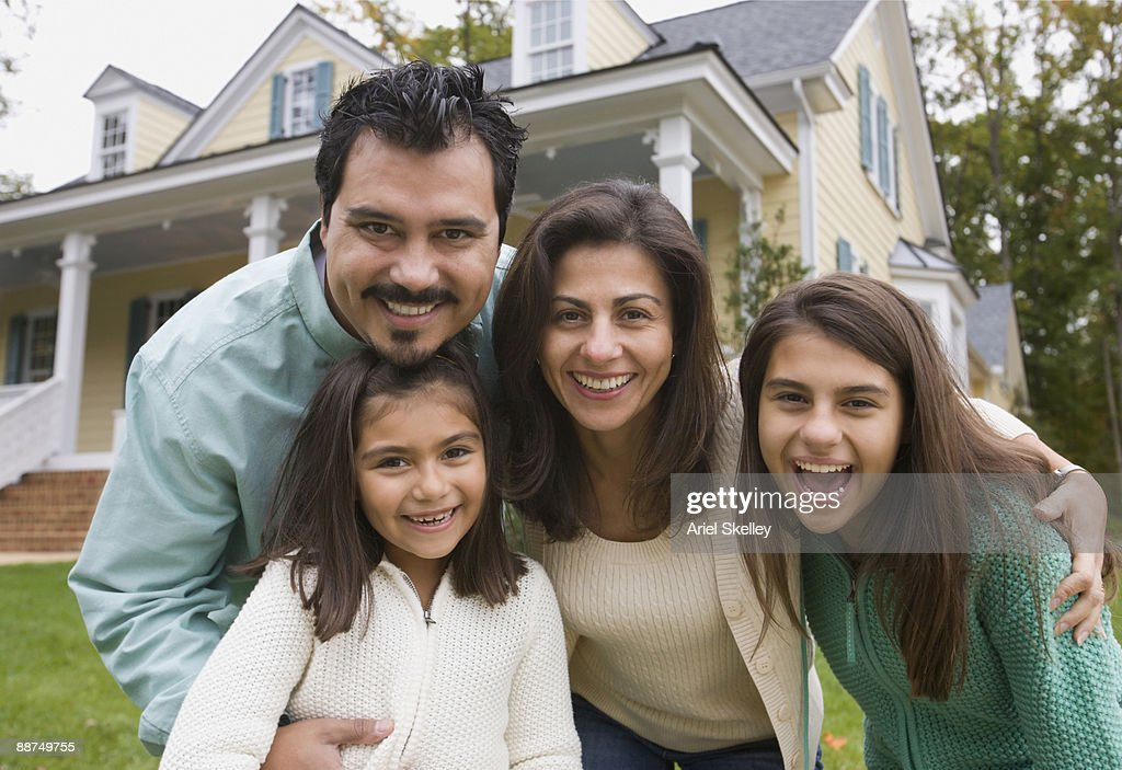 hispanic family posing in front of house stock photo