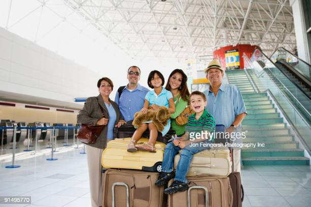 Hispanic family posing with luggage in airport