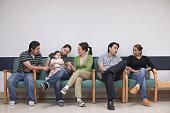 Hispanic family sitting in waiting room