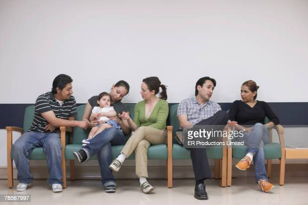 Hispanic family sitting in waiting room