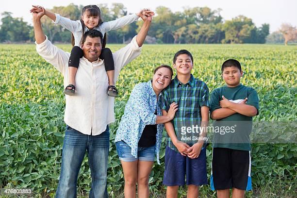 Hispanic family smiling in crop field