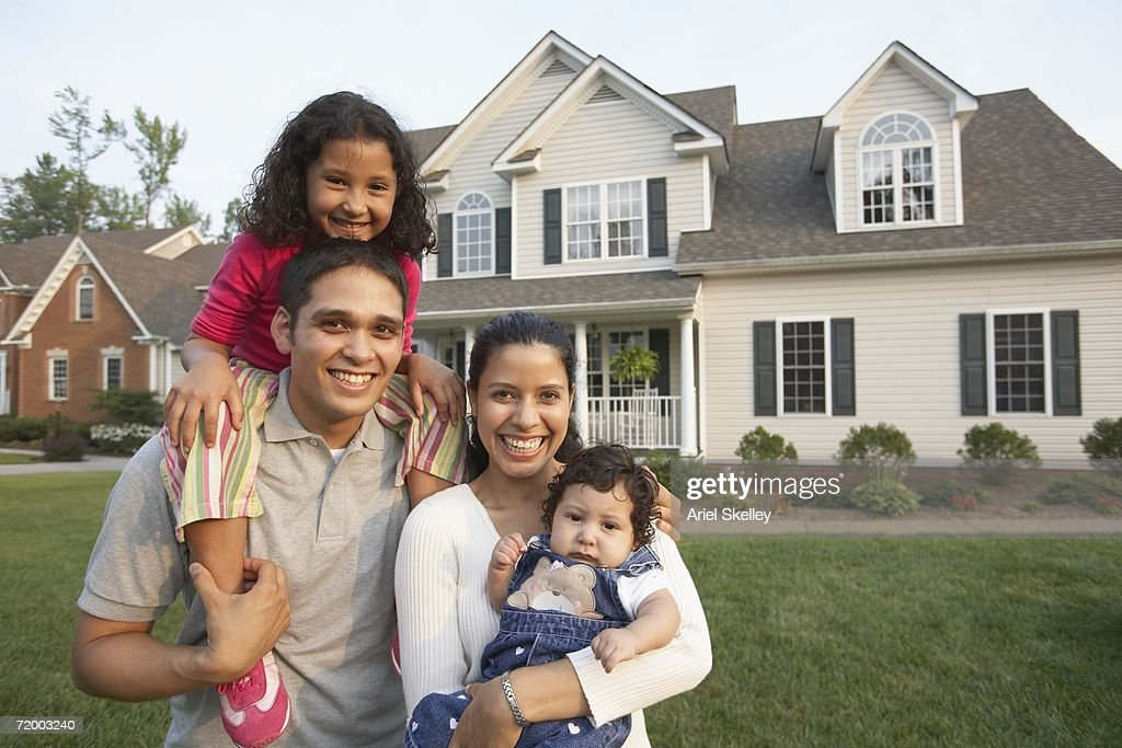 hispanic family smiling in front of house stock photo