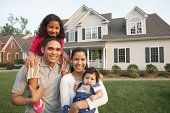 Hispanic family smiling in front of house