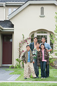 Hispanic family smiling outside home