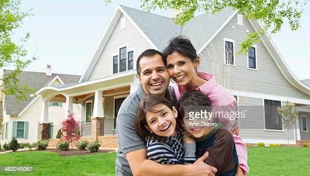 Hispanic family smiling outside house