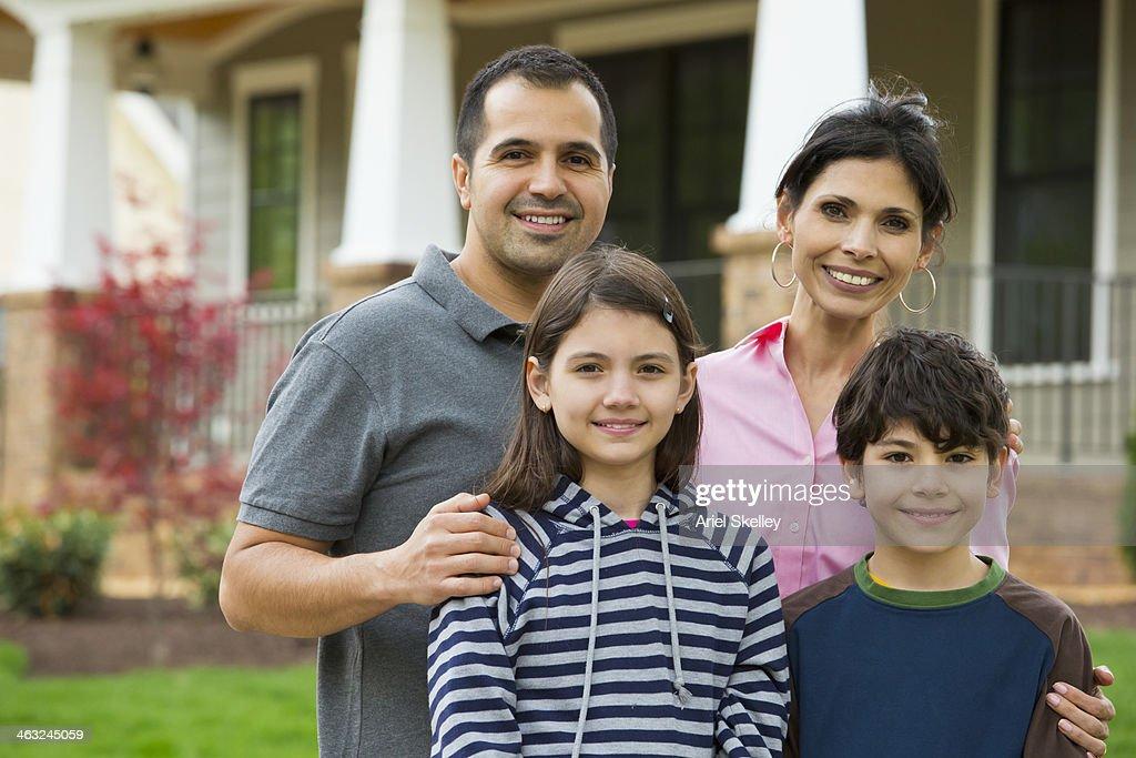Hispanic family smiling outside house : Stock Photo