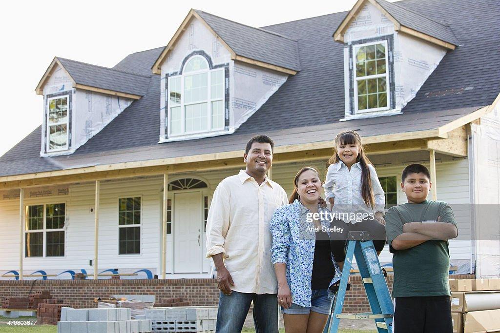 Hispanic family smiling outside house under construction : Stock Photo