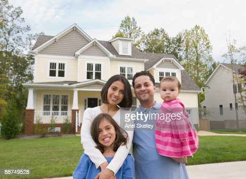 hispanic family standing in front of house stock photo