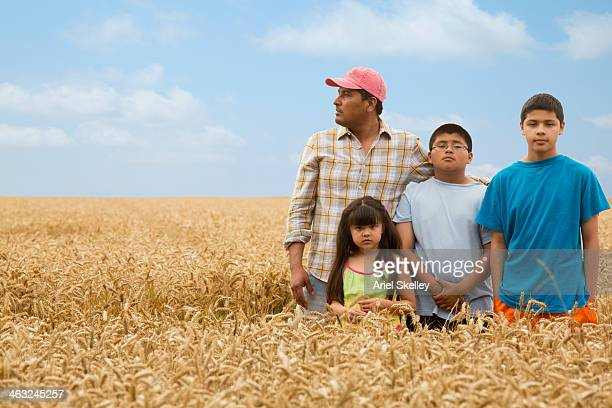 Hispanic family standing in wheat field