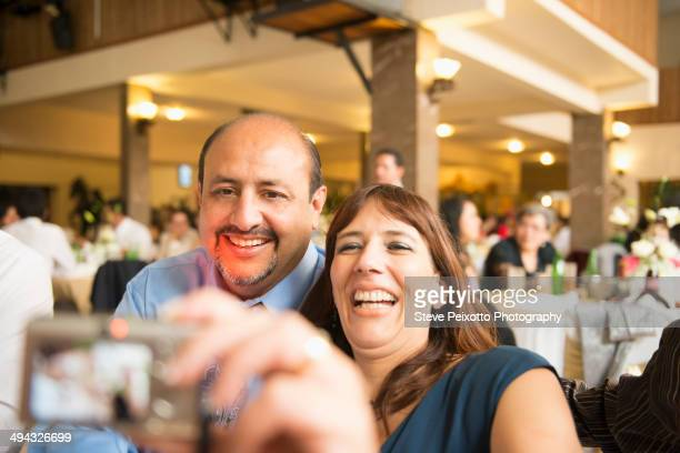 Hispanic family taking pictures at wedding reception
