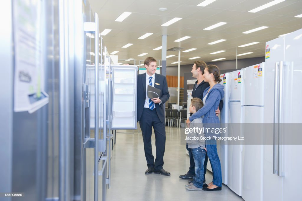 Hispanic family talking to salesman in appliance department : Stock Photo