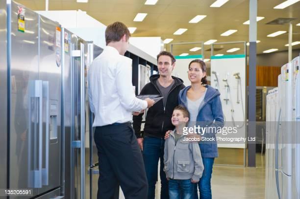 Hispanic family talking to salesman in appliance department