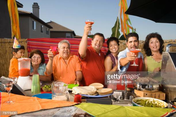 Hispanic family toasting at party outdoors