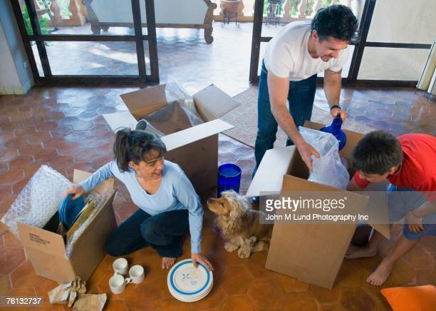 Hispanic family unpacking moving boxes