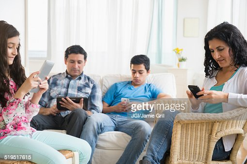 Hispanic family using cell phones and digital tablets in living room
