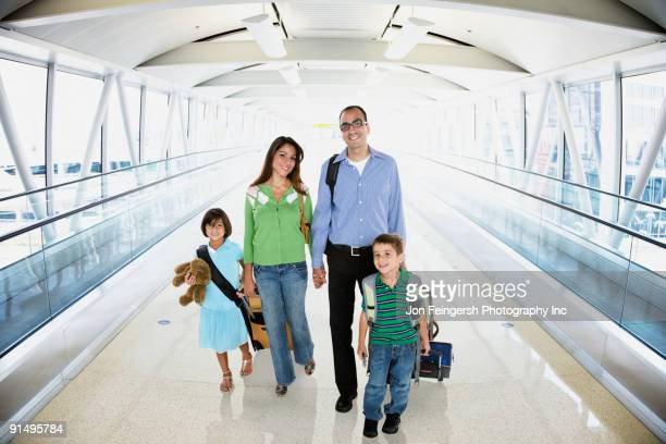 Hispanic family walking in airport