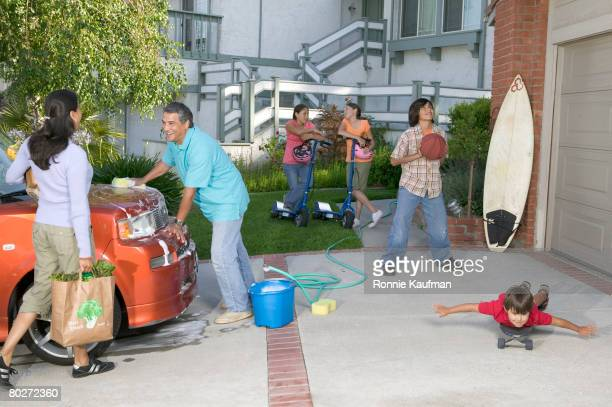 Hispanic family washing car and playing