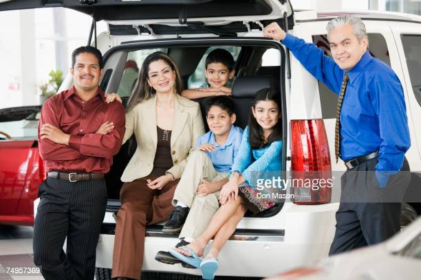 Hispanic family with salesman at car dealership