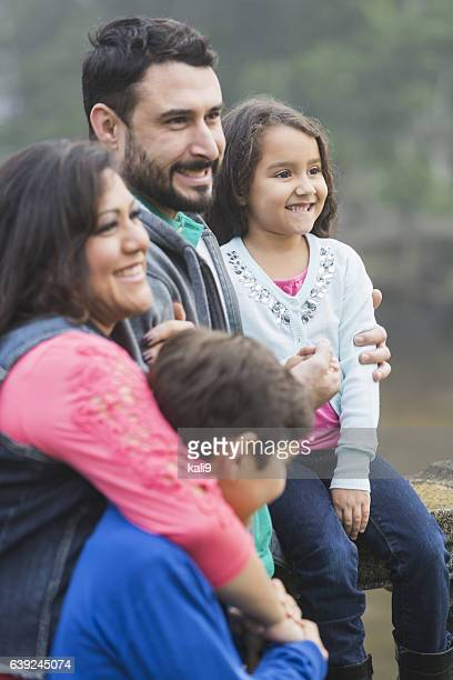 Hispanic family with two children posing outdoors