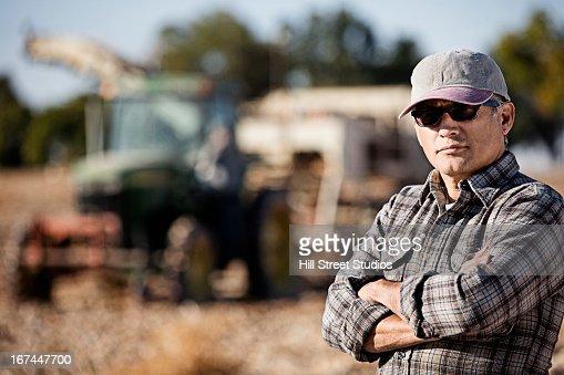 Hispanic farmer standing by harvester : Stock Photo