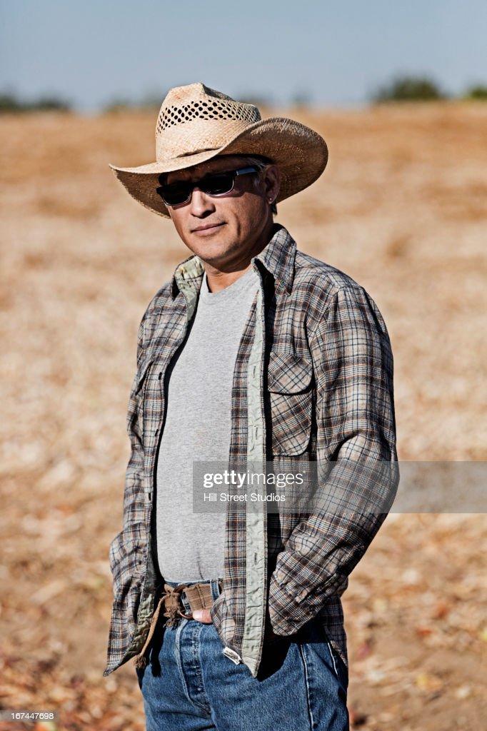 Hispanic farmer standing in crop field : Stock Photo
