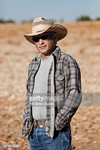 Hispanic farmer standing in crop field : Stock Photo