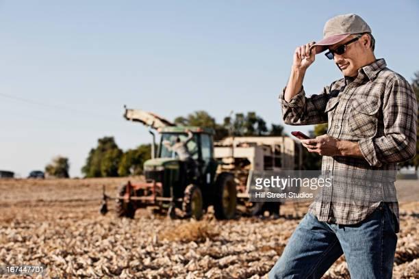 Hispanic farmer using cell phone in crop field