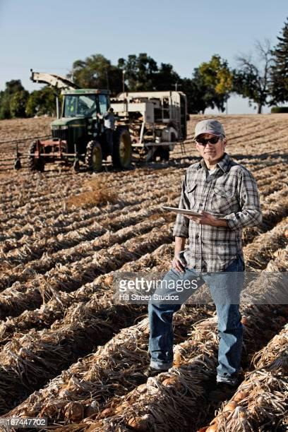 Hispanic farmer using tablet computer in crop field